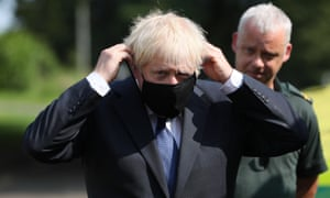 Boris Johnson puts on a face mask during a visit to the Northern Ireland ambulance service headquarters in Belfast.
