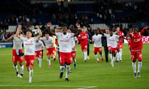 Reims players run towards their fans after beaing PSG 2-0 in the Parc des Princes.