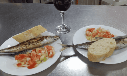 Seafood dishes and a glass of red wine on a serving counter at La Barraquilla, Almeria, Spain.