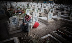 A mourner sits next to the grave of his son in a Baghdad cemetery.