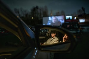 A couple seen through their car's door mirror. People have had to wait for up to two hours for tickets, due to the growing demand for drive-in film screenings.