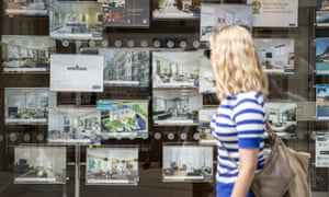 A woman looking in an estate agent's window