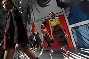 A model on the Prada catwalk. The show space was decorated with cartoons of female characters.