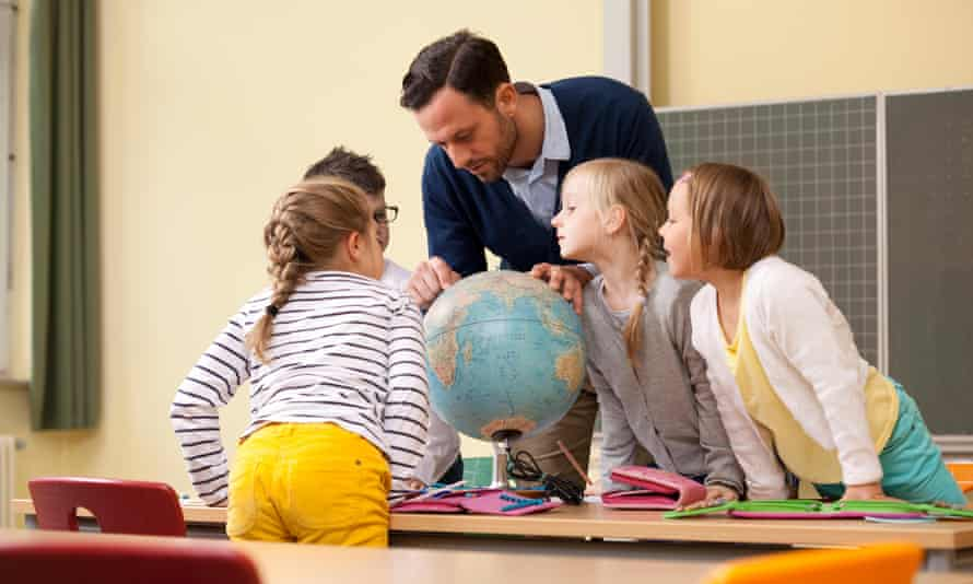 teacher looking at globe with students