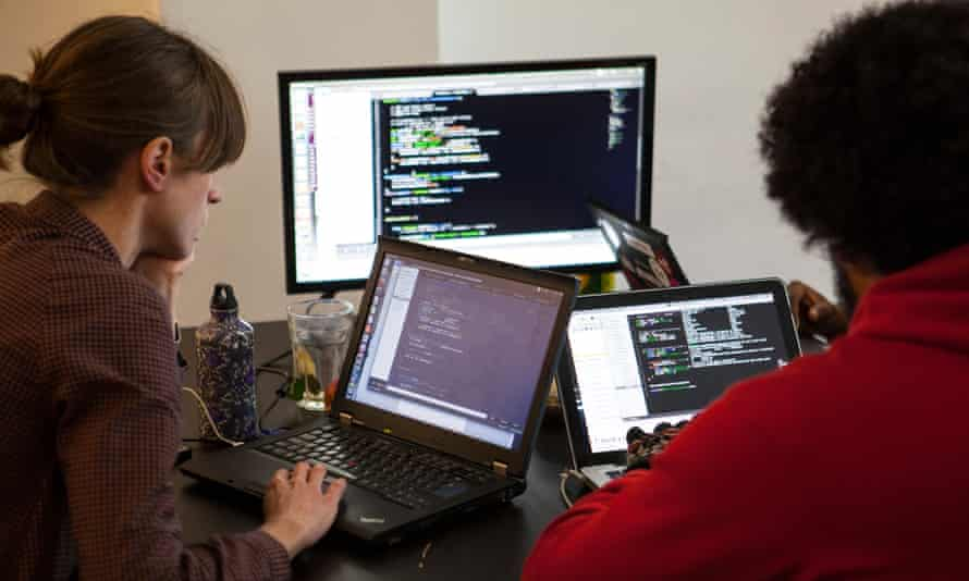 a young man and woman code on their laptops