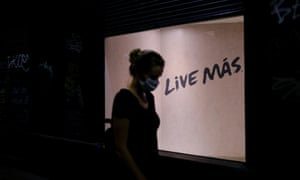 "A woman walks past a sign reading ""Live More"" on a street in Barrio Gotico after Catalonia's regional authorities announced restrictions to contain the spread of Covid-19 in Barcelona, Spain."