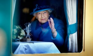 The Queen waves from a train carriage window at Edinburgh's Waverley station.