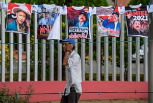 A man walks in front of t-shirts with pictures of Nicaraguan President Daniel Ortega and other leaders in Managua, Nicaragua.