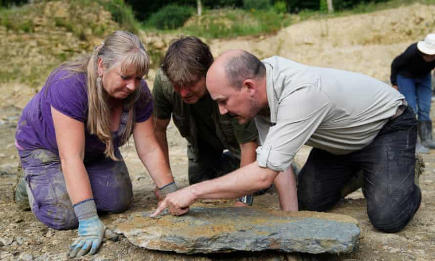 Three people leaning over a chunk of rock