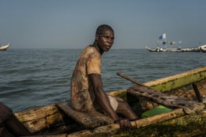 Eric Quaye Ade, a Ghanaian fisherman, sits in his boat in the waters at the Gulf of Guinea where he has been working for almost twenty years.