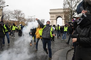 A demonstrator throws a tear gas canister at the Arc de Triomphe