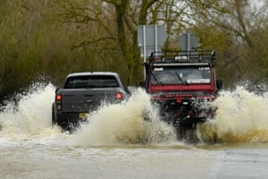 Vehicles navigate a flooded lane in Leicestershire