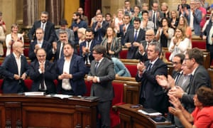 Catalan regional president, Carles Puigdemont (fourth from left) applauds with MPs after a referendum law was approved by the Catalonian parliament.