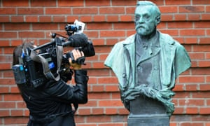 A woman films a statue of Swedish inventor Alfred Nobel