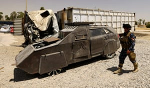 A police officer walks past a suicide bomb car