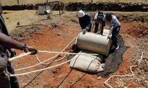 Workers use a barrel to crush sacks filled with harvested desert locusts, at a farm near Rumuruti.