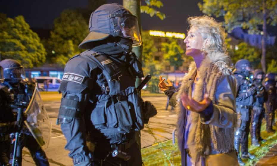A woman talks to a policeman in Hamburg's Schanzenviertel quarter on Tuesday night.