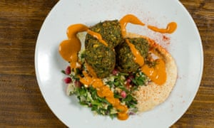 Three falafels on a mound of hummus with tabbouleh and harissa drizzled over the top