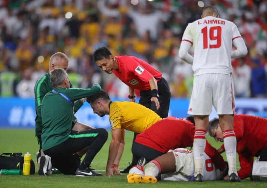 Mathew Leckie of Australia and Fares Juma Al Saadi of United Arab Emirates receive treatment in their Asian Cup match.