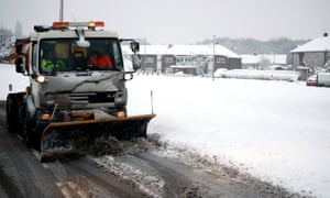 A snow plough works to clear roads