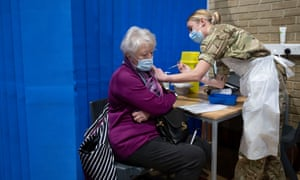A member of the military vaccinates a woman in Cardiff, Wales.