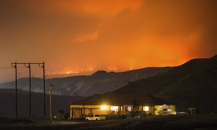 A wildfire burns on a mountain in the distance east of Cache Creek