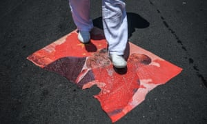 A demonstrator steps on a poster of Chinese President Xi Jinping and Chinese communist leader Mao Zedong during a Uighur protest in Istanbul