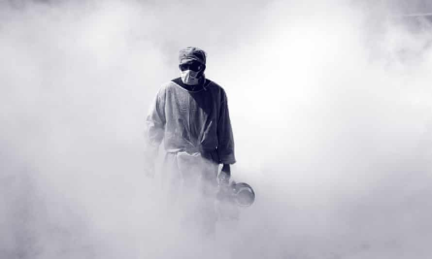 A health worker sprays disinfectant in a market street in India.