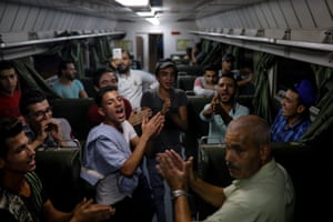People sing while they travel by train through the outskirts of Damascus towards a recently opened international fair.
