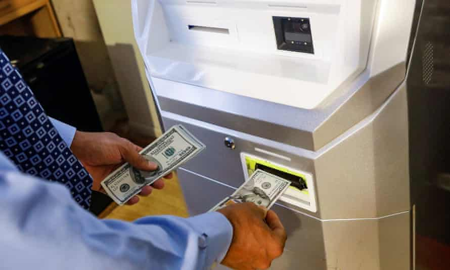 A man feeds money into a Bitcoin machine in New York, US.
