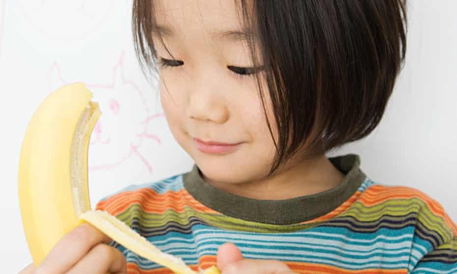 A boy peels a banana