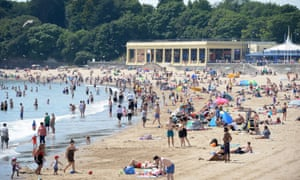 Sunbathers pack the beach at Barry Island, south Wales, on Monday.
