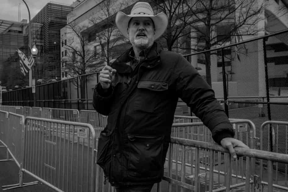 A pedestrian watches national guard troops march down Pennsylvania Ave on 17 January.