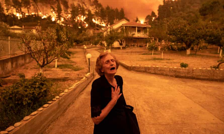 An elderly resident reacts as a wildfire approaches her house in the village of Gouves, on the island of Evia, Greece