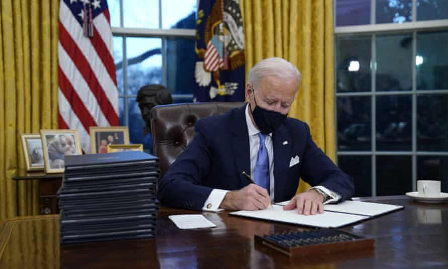 Joe Biden signs an executive order on 20 January. The White House has called the Covid relief bill 'the most progressive legislation in history'.