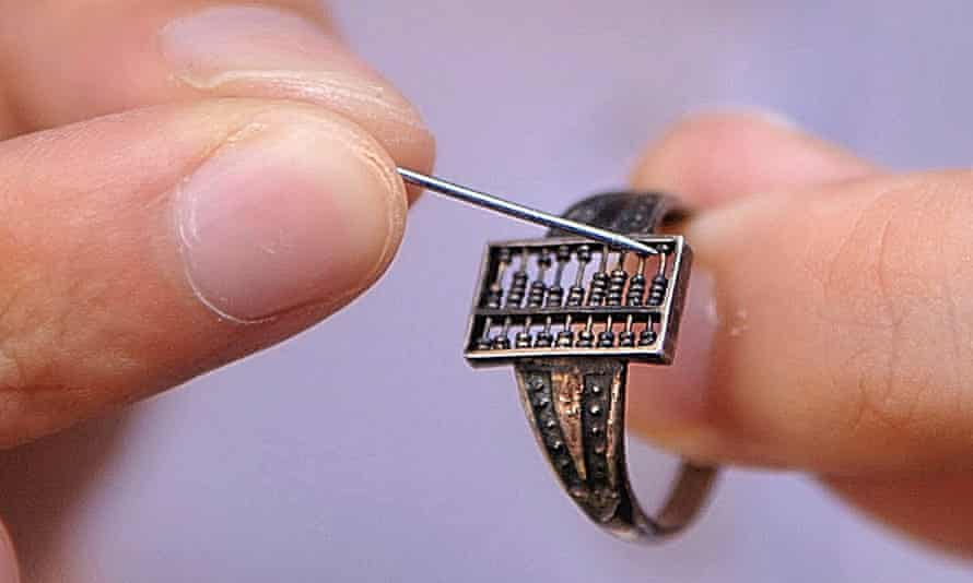 A person uses a pin to move the beads of a silver ring abacus of 1.2 centimeter long and 0.7 centimeter wide, dating back to Chinese Qing Dynasty