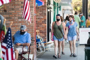 People walk down the sidewalk in St Simons Island, Georgia, on 17 July. Brian Kemp made an order earlier in the week that forbade municipal officials from setting mandatory face-covering policies.