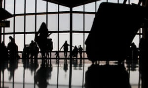 Silhouettes of travellers at a US airport