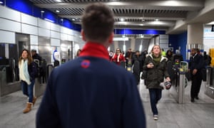 A member of station staff watches passengers at Tottenham Court Road