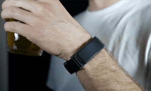 BACtrac Skyn wearable device being worn by a man holding a drink