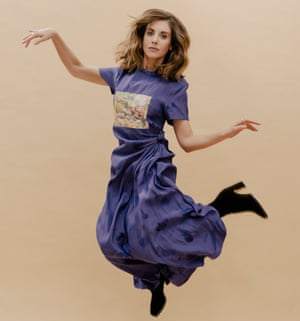 Alison Brie jumping, with arms and legs cocked, in a long, mauve T-shirt dress with full skirt gathered at the waist and heeled lack boots