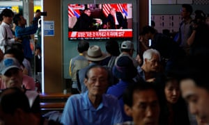 People watch TV coverage of the Trump-Kim meeting at a station in Seoul