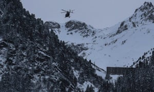 A helicopter flies to the site of the avalanche near Valfréjus