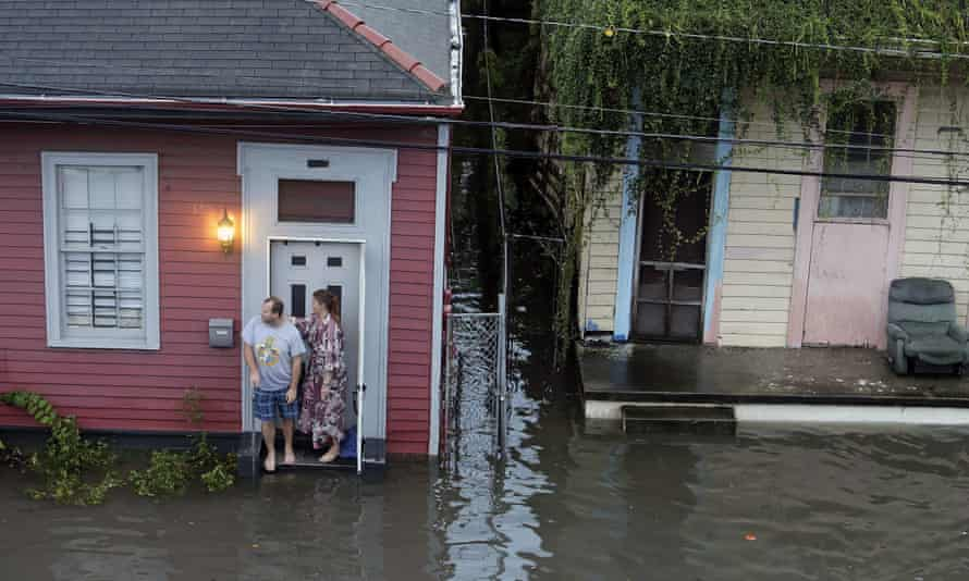 People stand outside their home in floodwaters in New Orleans on 5 August.