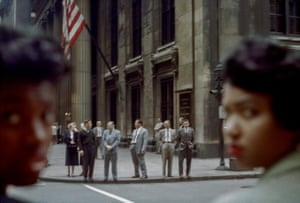 In the background and in focus: several men in suits waiting to cross the road, beneath an American flag. In the foreground and blurred: two black women looking back over their shoulders at the camera.