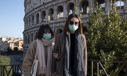 Tourists wearing face masks visit the Colosseum area in Rome, where England are scheduled to play on 14 March.