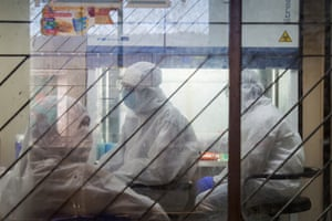 Health workers in white protective suits collect coronavirus samples at a local hospital in Dhaka