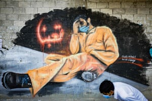 """A youth, wearing a protective mask, walks past a mural reading """"We are tired"""" in Tripoli, Lebanon"""