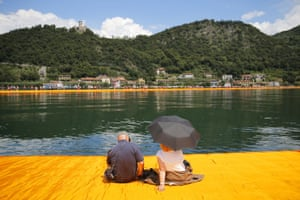 A couple sit on the pier with an umbrella