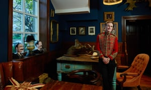 Mark Hinchliffe wearing a military jacket in the 'gentlemen's club room' with dark blue walls
